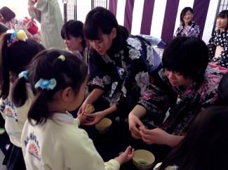生徒が園児にお茶の点て方を教えています
