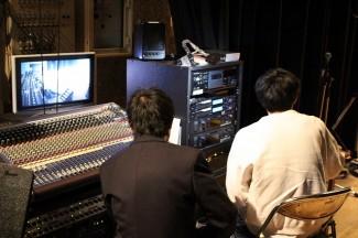 舞台を見ながら音を出すタイミングを確認する音響スタッフの生徒