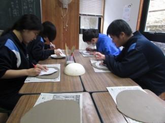 粘土に型紙でイラストを描いている様子