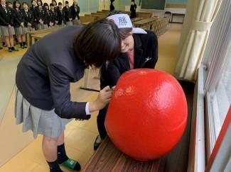 生徒代表の吉留さんと担任の小林先生が必勝だるまの片目を描きました☆